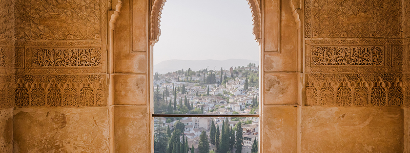 A Spanish town in the distance framed by an archway