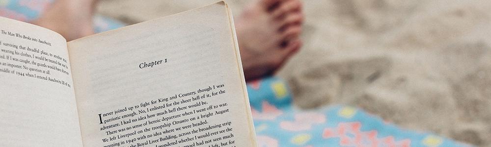 A book being read on a sandy beach